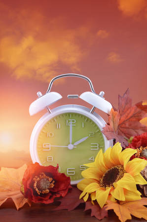 daylight: Autumn daylight saving time concept with green clock on natural wood table with sunset sky background, and added vintage style filters and lens flare. Stock Photo