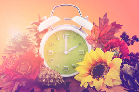 fall leaves: Autumn daylight saving time concept with green clock on natural wood table with sunset sky background, and added vintage style filters and lens flare, closeup.