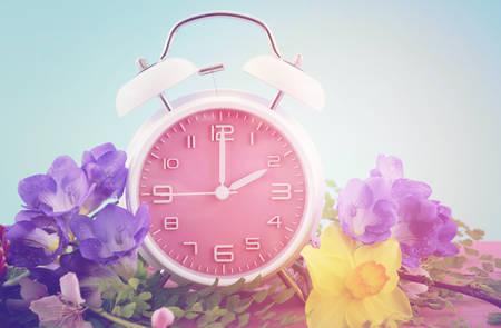추가 빈티지 스타일 필터와 렌즈 플레어 푸른 하늘 배경으로 분홍색 나무 테이블에 핑크 시계와 봄 일광 절약 시간 개념. 스톡 콘텐츠