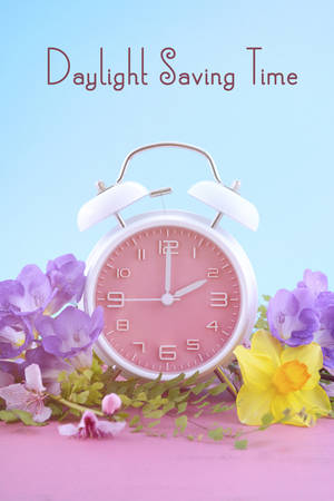 blossom time: Springtime daylight saving time concept with pink clock on pink wood table with blue sky background, with sample text.
