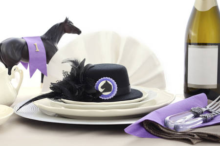 royals: Horse racing Ladies Luncheon fine dining table setting with small black fascinator hat, decorations and champagne.