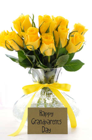 yellow roses: Yellow roses gift in vase with greeting card and sample text for Grandparents Day on white vintage wood table. Stock Photo