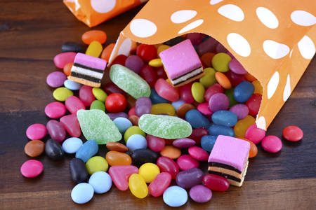 Halloween Party Trick of Treat Candy with candy flowing from orange polka dot party favor bag on dark wood background.