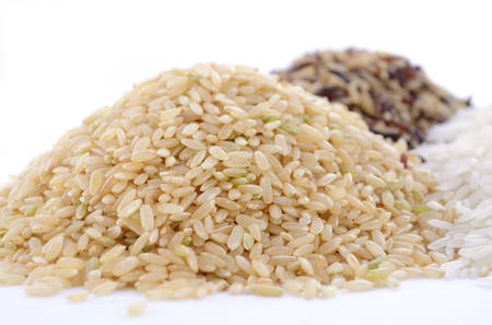 Stacks of raw gluten-free rice cereal ingredient, including white, brown, red and black rice grains on white table and background, with focus on brown rice. Stockfoto