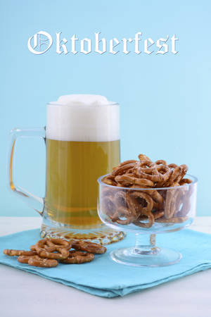 superbowl: Glass of beer in stein with mini pretzels on pale blue napkin on pale blue and white wood background with sample text.