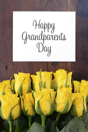Yellow roses gift for Grandparents Day with greeting card on dark cintage wood table. Stock Photo