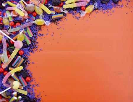 할로윈 트릭이나 트리 트먼트, 또는 어린이 생일 파티 호의 가방에 대 한 복사 공간이 오렌지 나무 배경에 밝은 다채로운 캔디.