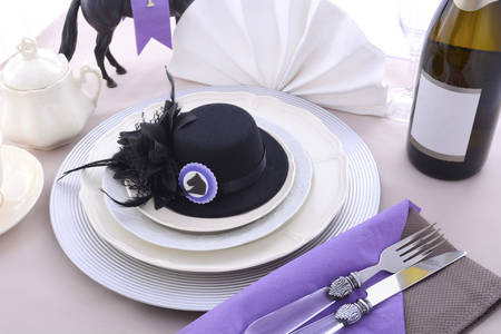 carreras de caballos: Señoras de carreras de caballos almuerzo de mesa de comedor cubierto con pequeño sombrero fascinator negro, decoraciones y champagne.