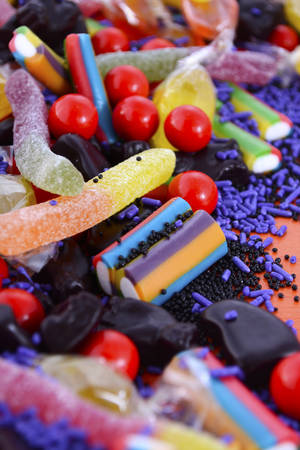colourful candy: Bright colorful candy closeup on orange wood background for Halloween Trick or Treat, or children birthday party favor bags.