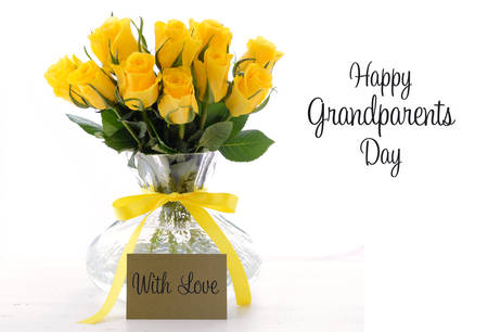bunch of: Yellow roses gift in vase with greeting card and sample text for Grandparents Day on white vintage wood table. Stock Photo