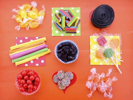 treats: caramelos de colores brillantes sobre fondo de madera de color naranja para el truco de Halloween o invitación o cumpleaños de los niños bolsas favor de partido.