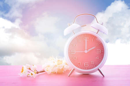 Springtime daylight saving time concept with pink clock on pink wood table with blue sky background, and added filters and lens flare.