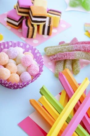 childrens birthday party: Pile of bright colorful candy on pale blue wood table for Halloween trick of treat or childrens birthday party favors. Stock Photo