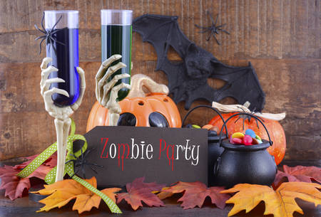 ghoulish: Happy Halloween Zombie Party decorations with green and blue drinks in skeleton hand glasses, pumpkins and candy on witches cauldrons on dark wood table background.
