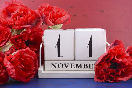 armistice: White block vintage calendar with large red Flanders poppies on red and blue wood background for Remembrance, Armistice and Veterans Day. Stock Photo