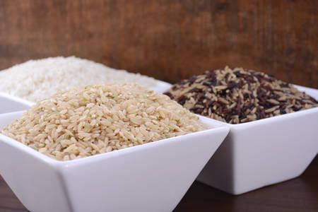 Cuencos cuadrados de arroz marrón, blanco, y rojo y negro sin cocer sobre fondo de madera oscura de la vendimia. Foto de archivo - 46754726