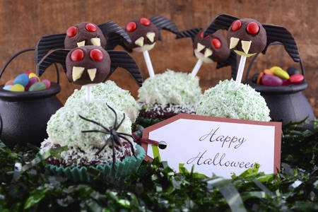 favor: Happy Halloween party cupcakes with ghoulish chocolate lollipop faces and mini licorice bat wing ears with candy in witches cauldrons on dark wood table background.