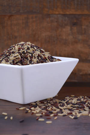 glycemic: Square bowl of uncooked red, black and brown rice on dark wood vintage background. Stock Photo