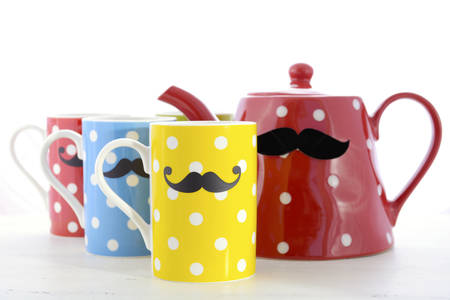 health awareness: Colorful polka dot coffee mugs with mustaches for November Mens health awareness, with large red coffee tea pot on white wood table.