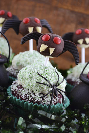 ghoulish: Happy Halloween party cupcakes with ghoulish chocolate lollipop faces and mini licorice bat wing ears with candy in witches cauldrons on dark wood table background.