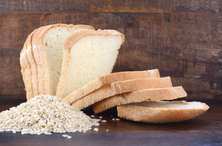 slices of bread: Gluten free rice sliced sour dough bread with raw brown rice on dark wood table background. Stock Photo