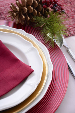 place setting: Traditional red theme festive table place setting for Christmas or Thanksgiving dinner party table.
