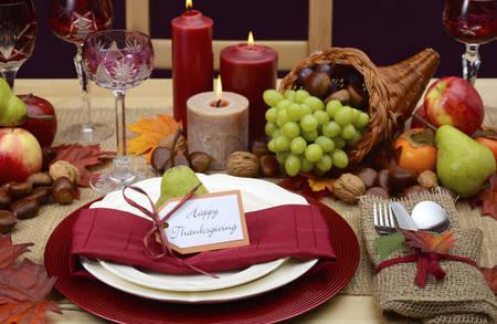Landelijke stijl rustieke Thanksgiving tafel met plaats instelling, hoorn des overvloeds, kaarsen en herfst fruit centerpice. Stockfoto