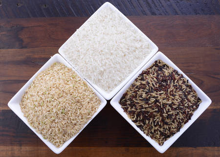 glycemic: Square bowls of uncooked brown, white, and red and black rice on dark wood vintage background, overhead view.