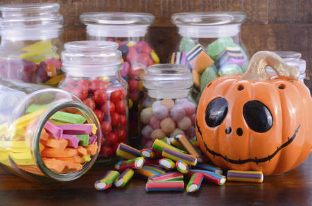 jack o lantern: Happy Halloween Candy in Glass Apothecary Jars with orange pumpkin Jack O Lantern closeup on dark wood table.