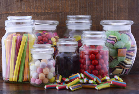 glass jars: Happy Halloween Candy in Glass Apothecary Jars on dark wood table.