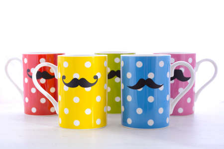 Colorful polka dot coffee mugs with mustaches for November Mens health awareness on white wood table.