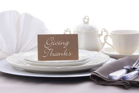 thanksgiving menu: Elegant Thanksgiving table place setting with fine china, crystal and antique cutlery in subdued colors with Giving Thanks place card holder.