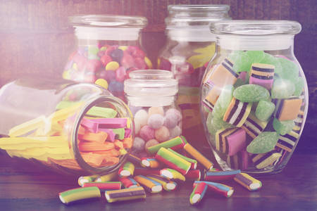 glass jars: Happy Halloween Candy in Glass Apothecary Jars on dark wood table, with added retro vintage filters and light stream lens flare.