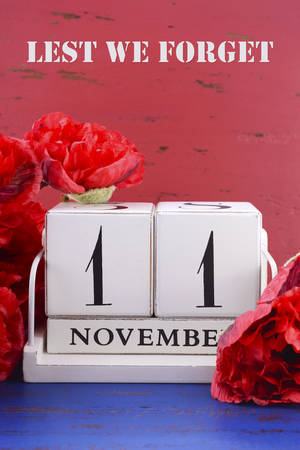 remembrance day poppy: White block vintage calendar with large red Flanders poppies on red and blue wood background for Remembrance, Armistice and Veterans Day, and Lest We Forget text.