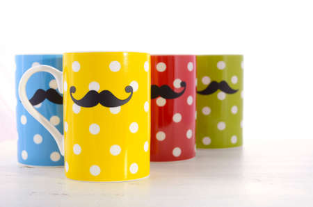 health awareness: Colorful polka dot coffee mugs with mustaches for November Mens health awareness on white wood table.