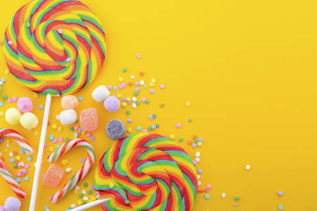 candies: Brillante caramelo lollipop del arco iris en la mesa de madera de color amarillo vivo para el truco de Halloween o invitación o fiesta para niños. Foto de archivo