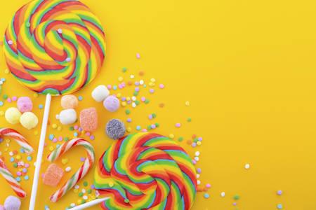 Heldere regenboog lollipop snoep op kleurrijke gele houten tafel voor Halloween Trick or treat of Childrens Party.
