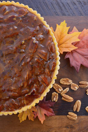 pecan pie: Happy Thanksgiving traditional pecan pie on vintage dark wood table and background with autumn leaves. Foto de archivo