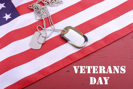 Veterans Day USA flag with dog tags on rustic red wood background with sample text. Stock Photo
