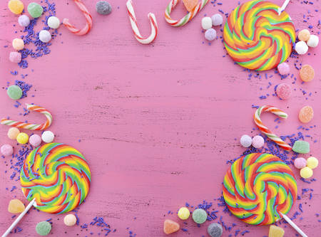 children birthday: Assorted candy and rainbow lollipop on pink wood rustic table background with copy space.