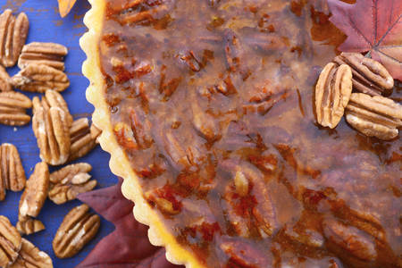 pecan pie: Happy Thanksgiving traditional pecan pie on vintage dark blue wood table and background with autumn leaves and extra nuts.