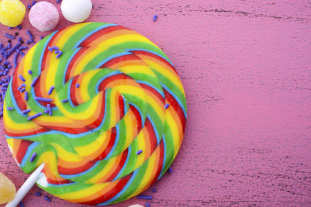 Assorted candy and rainbow lollipop on pink wood rustic table background with copy space.