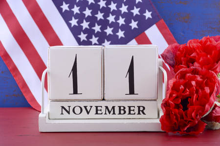 white day: Vintage style wood block calendar for November 11, USA Veterans Day, with Stars and Stripes flag  and red Flanders poppy flowers for remembrance on red and blue wood background.
