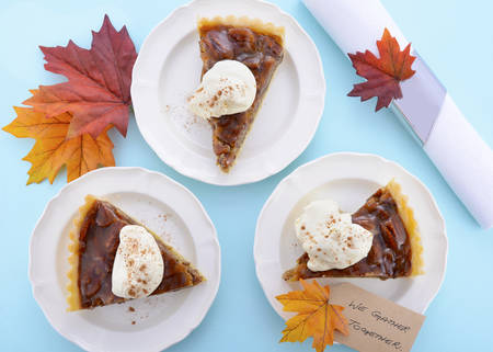 pecan pie: Happy Thanksgiving traditional pecan pie individual servings on pale blue wood table, overhead.