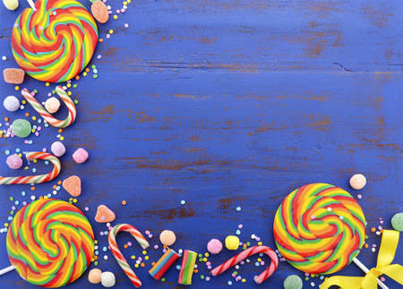 Bright rainbow lollipop candy on dark wood table.