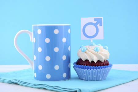 red velvet cupcake: International Mens Day Cupcake with Male Symbol with pale blue polka dot coffee mug on blue and white wood background.