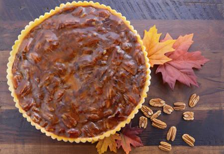 pecan pie: pastel de pacana tradicional de Acci�n de Gracias feliz en la mesa de madera oscura de la vendimia y de fondo con hojas de oto�o.