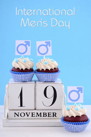 fathers day: International Mens Day Cupcakes with Male Symbols with vintage wood calendar for November 19 on pale blue and white wood background, and sample text.