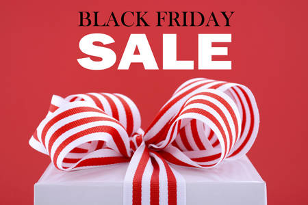 a sign: Black Friday red and white sales promotion gift box closeup against a red background with sample text.