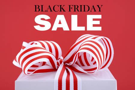 Black Friday rode en witte sales promotion gift box close-up tegen een rode achtergrond met voorbeeld tekst. Stockfoto